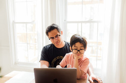 Canva - Father helping son study at home