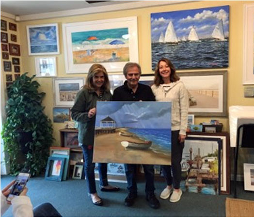 "H. Hargrove takes a photo Gina at Jersey Shore Moments Gallery in Manasquan with her new H. Hargrove painting, ""Spring Lake Beach."""