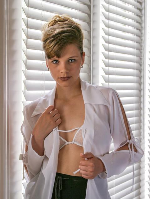 Woman by window removing white blouse - Medford photographer, John Neilson