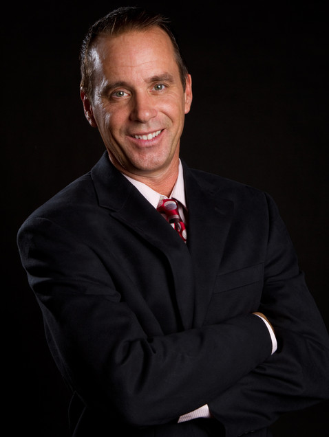 Business headshot of man in black suit on black background - Medford photography