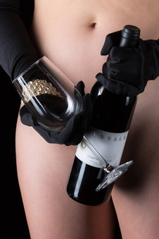 Black gloves holding wine bottle and glass