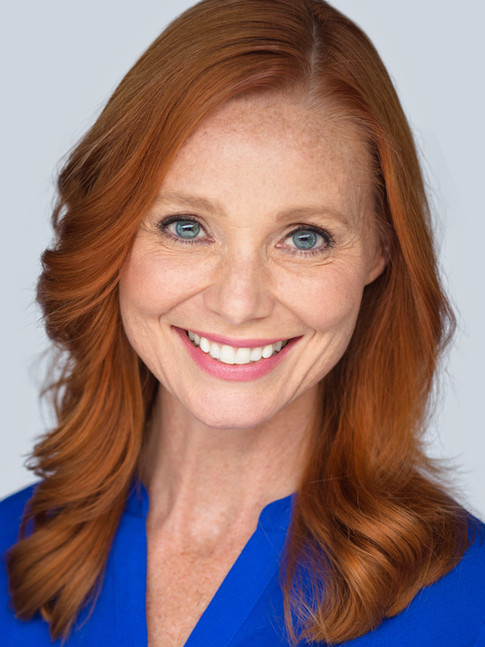 Business headshot of woman with red hair in blue shirt - Medford photography