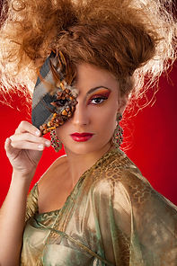 Medford, Oregon creative fashion photography - Woman in gold outfit with red hair holding mask
