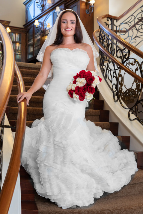 Brunette bride in ruffled mermaid gown coming down staircase at Belle Fiore Winery, Oregon - by Southern Oregon Photographer, John Neilson of Oregon Studio Group