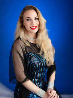 Blonde woman in blue sequin gown on blue backdrop - Medford photographer, John Neilson