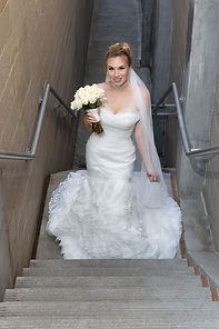 Medford, Oregon wedding photography - Bride in mermaid gown coming up stairs with white bouquet