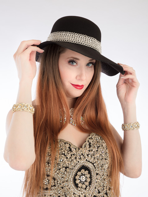 Red-haired woman in black and gold gown with black hat - Medford photographer, John Neilson