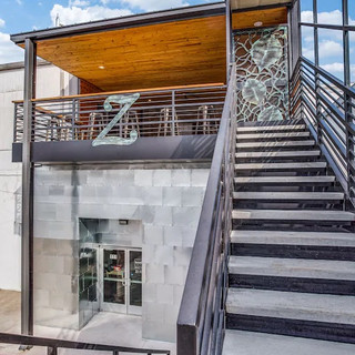 Stairs & entrance leading up to the covered plaza deck, located on the backside of the building with extra parking spaces available.