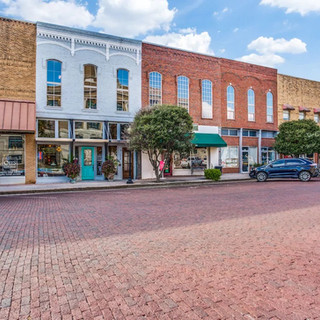 View of the beautiful cobblestone streets that line the Downtown Gainesville Square.  The 2nd story of the white brick building (above the turquoise door) is Loft Zaza.