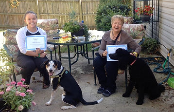 two dogs posing with people holding graduation certificates