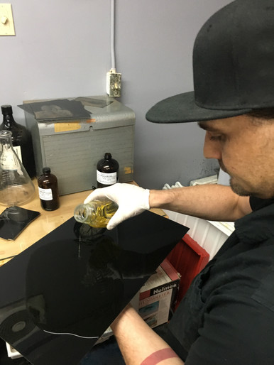 Sage pouring collodian on a large plate