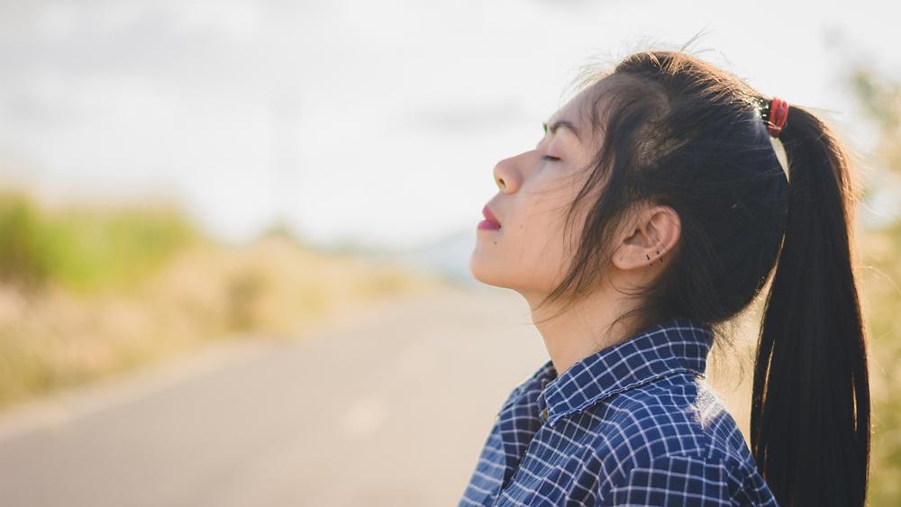 A woman standing taking a deep breath.