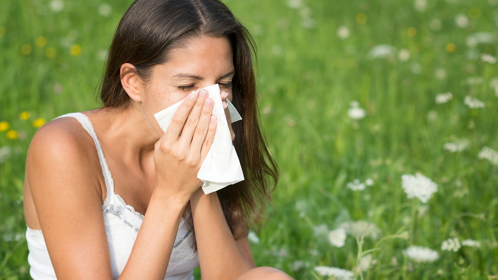 A lady sitting in a field of flowers, sneezing into a tissue.