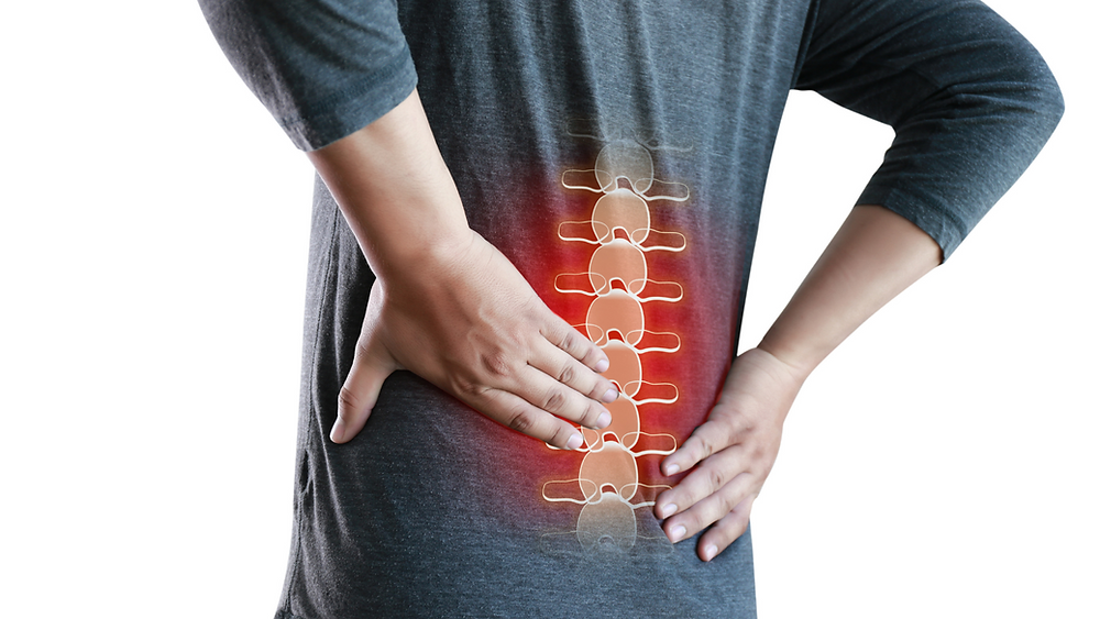 A man with his hands on his lower back symbolising back pain.