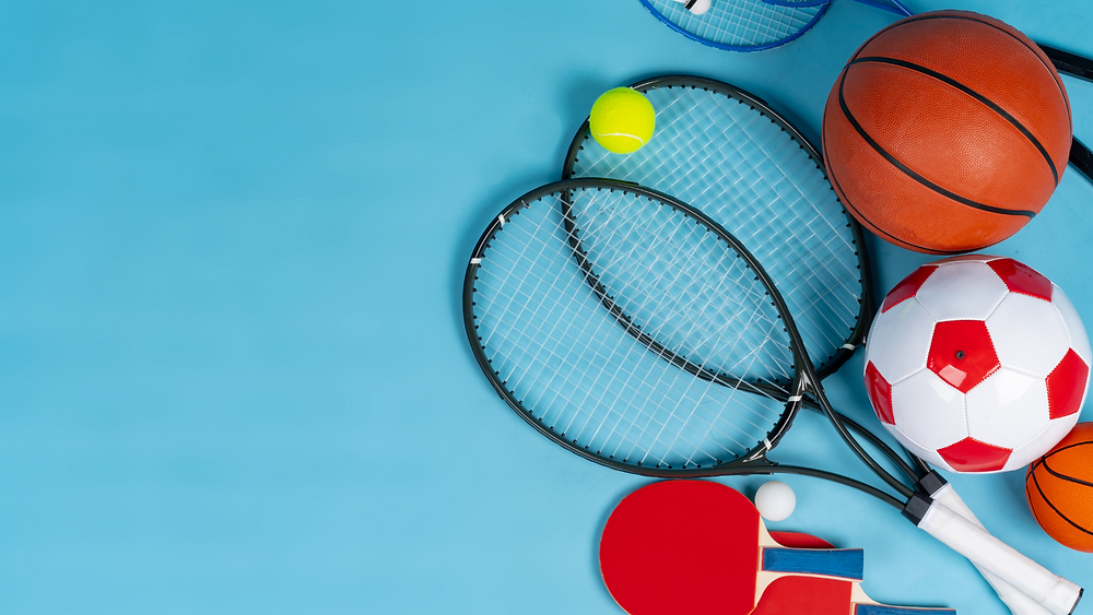 A variety of sports equipment including, tennis rackets, basketball, football and table tennis bats.