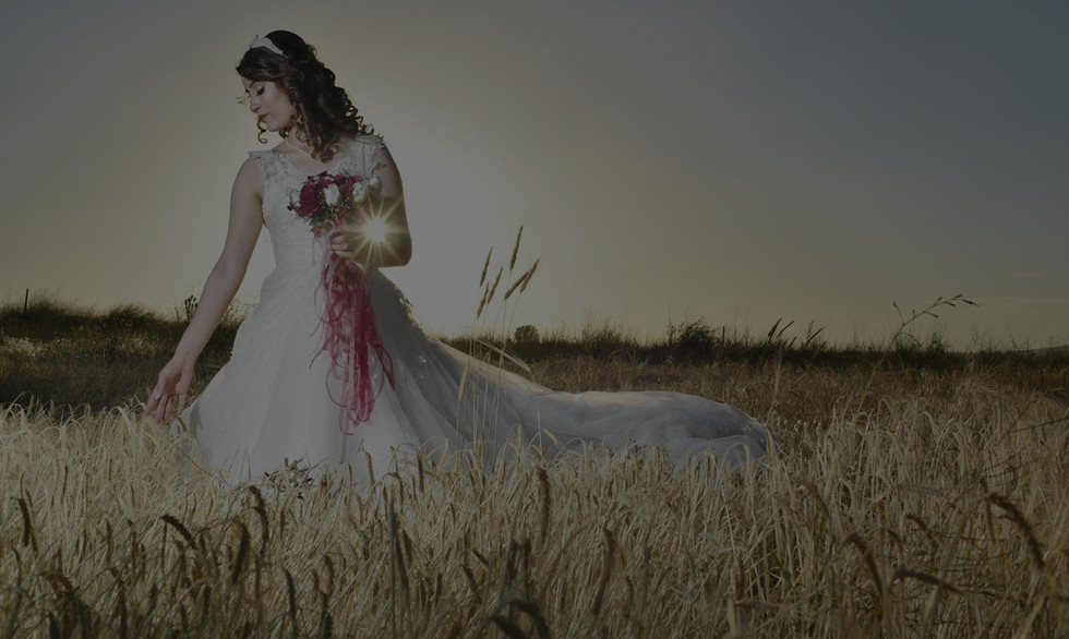 Young bride wearing a white wedding dress and holding a bouquet of roses posing in wheat field at sunset
