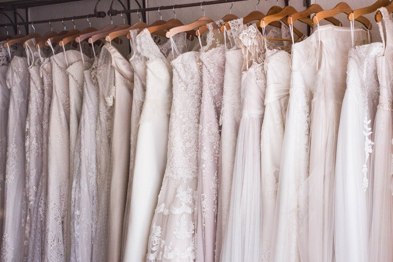 Lace wedding dresses of various designs hang side by side on a railing inside a bridal boutique