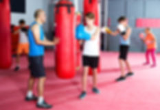 Smiling boxing instructor and children p