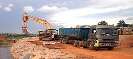 A truck deliverying stone base during a highway expansion project in Kampala