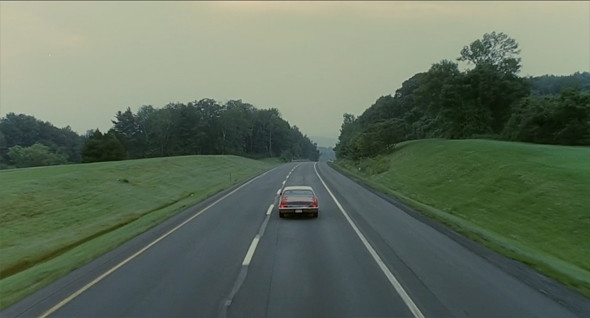 A car driving away down an empty road. Trees and grass grow on both sides of the two-lane road.