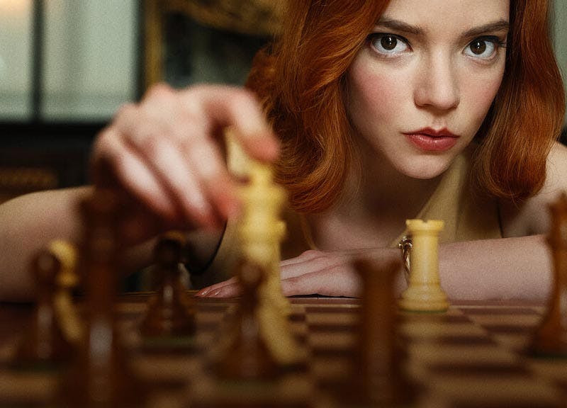 A young woman looks at the camera while she moves a white chess piece to a new position on a chess board.