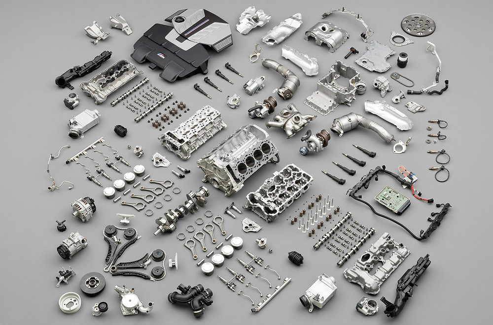 All the parts of an engine, taken apart and laying next to each other on a gray background