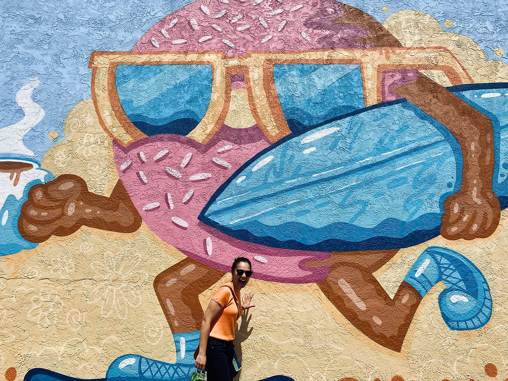 A woman playfully posing in front a surfing donut mural