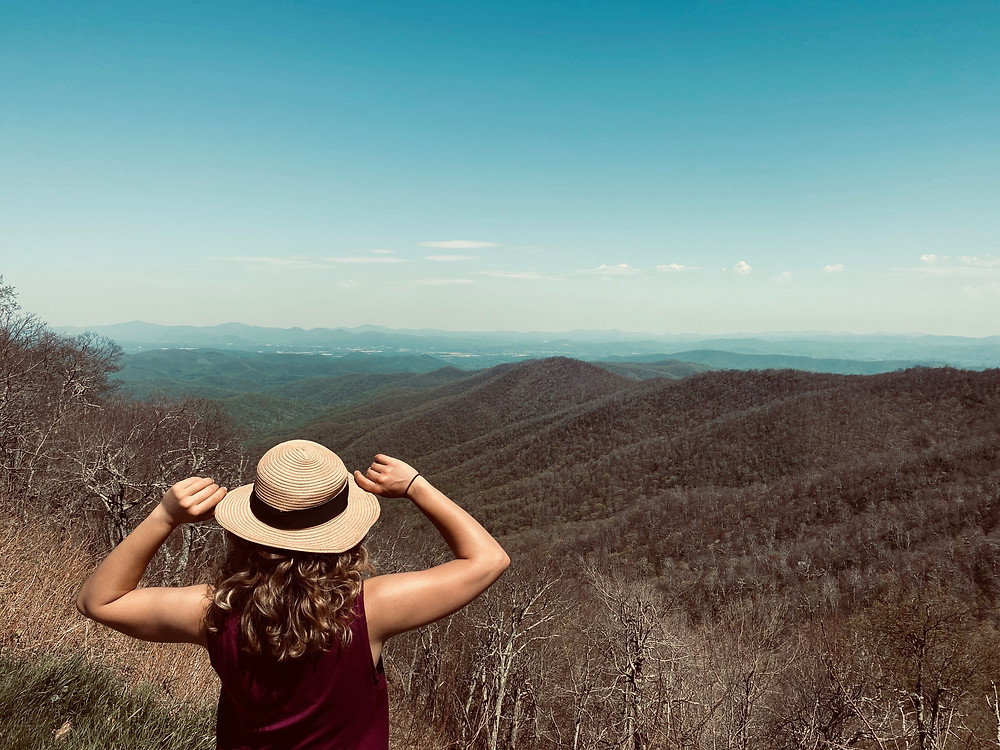 Strong woman looking at the mountains dreaming to achieve her goals. Personal growth, consciousness, managing your mind.