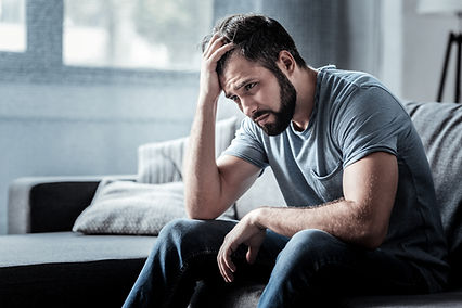 Unpleasant pain. Sad unhappy handsome man sitting on the sofa and holding his forehead whi