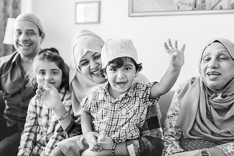 Muslim mother smiling at her son infront of her. The little boy is smiling with his hanf raised in the air