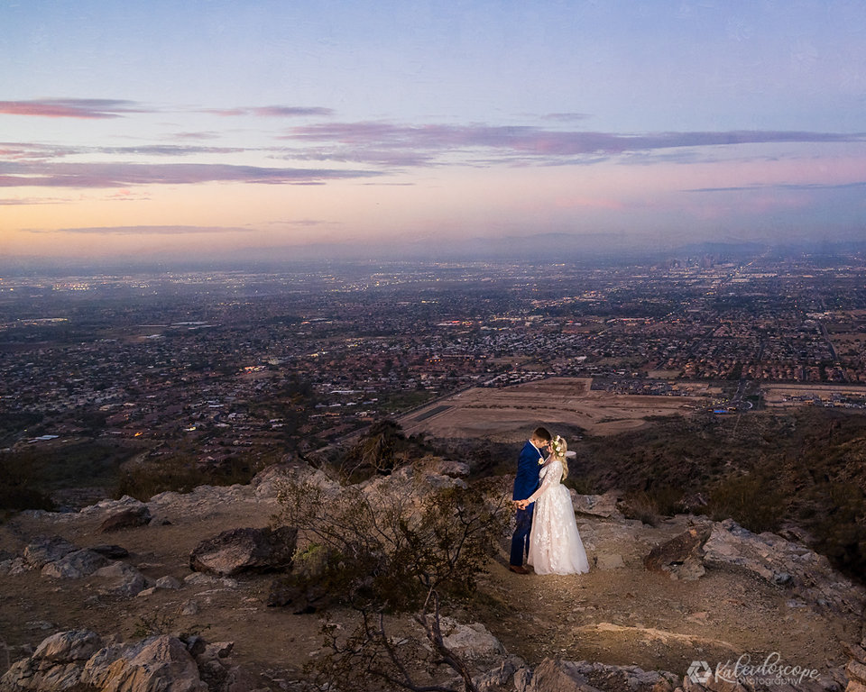 A Bride and Groom celebrating thier wedding in Scottsdale by dancing and looking into eachother eyes of the Arizona purple sunset