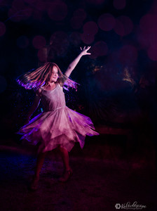 Young daughter dancing in white dress in the desert botanical gardens in phoenix being creatively lit by purple and pink.