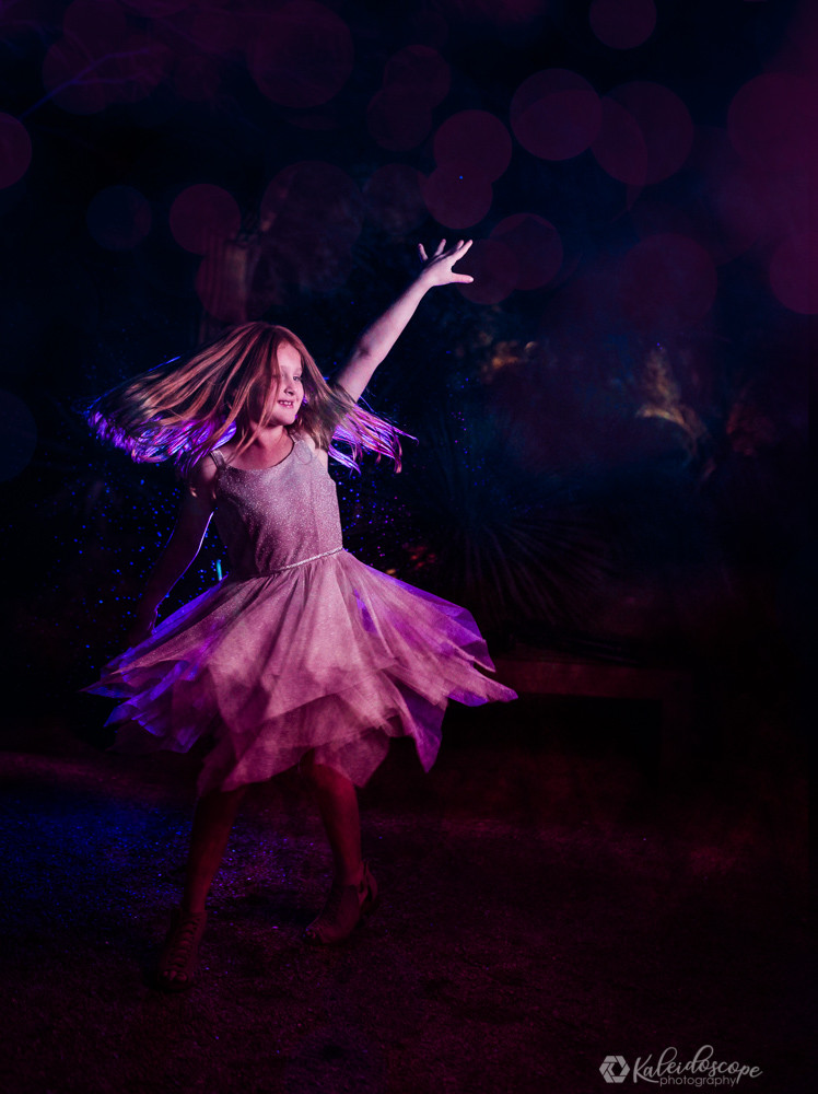 the purpose of portrait photography is this photo. A little girl wearing a white dress being illuminated by purple and other similar colors.