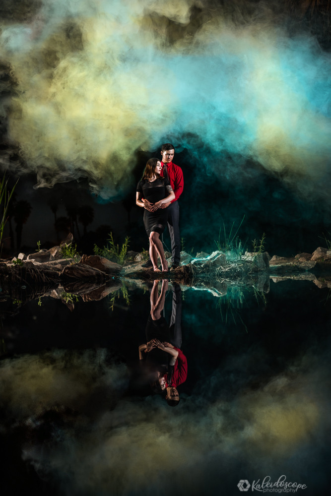 A creative engagement photo with smoke around them. The smoke is illuminated blue and yellow while the couple are holding each other. Their reflection is clearly visible in the water. This photo is created at Papago Park