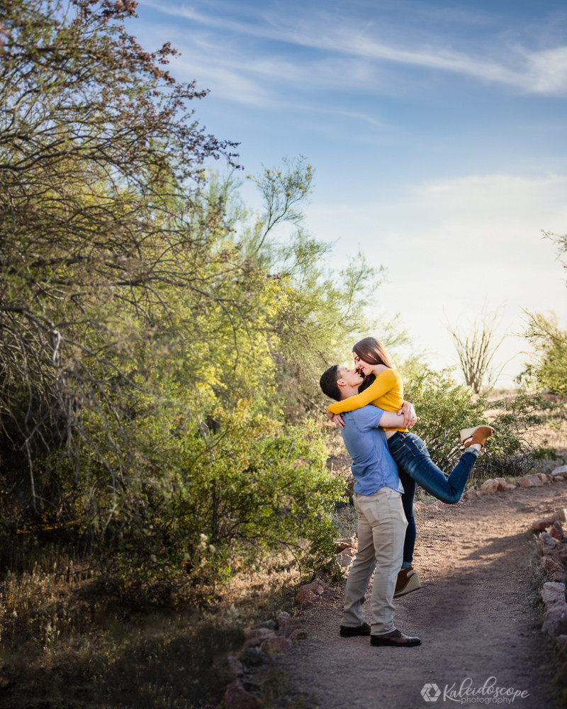 girl jumping onto her fiance and locking eyes in the Arizona desert