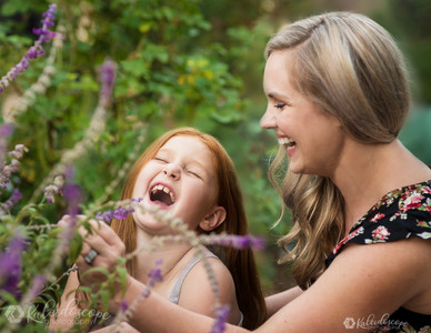 Scottsdale family photographer using lighting to and posing to show the connection between mother and daughter laughing while picking flowers at the desert botanical garden in phoenix in arizona