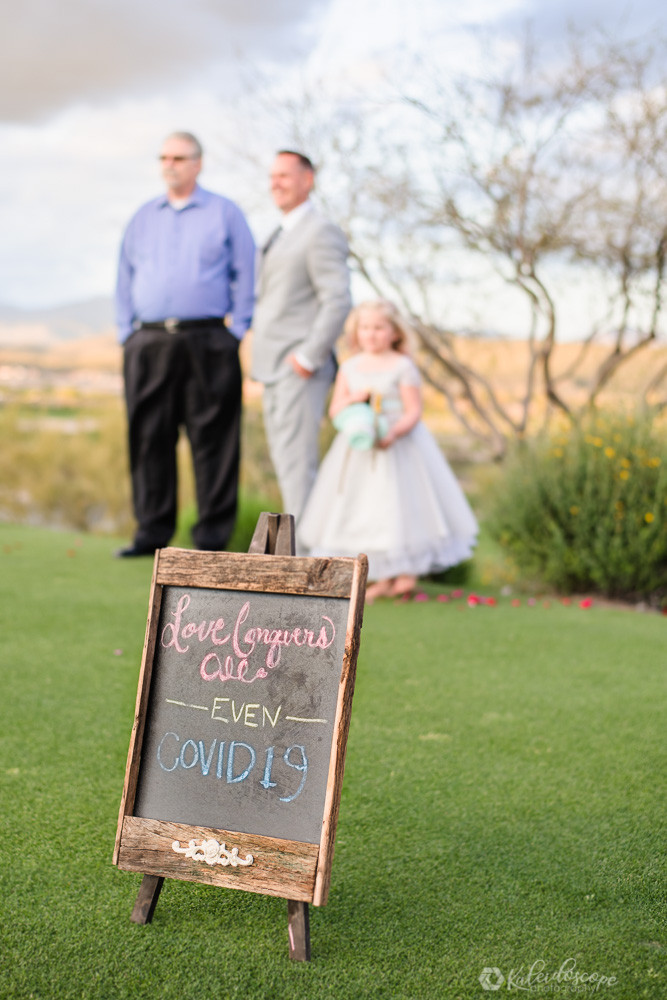 A sign displaying love conquers all even COVID19 with the groom and daughter in the background bokeh