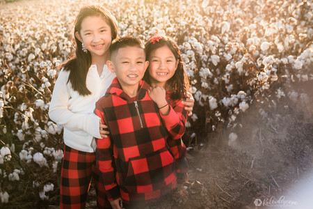 Siblings holding eachother and smiling in front of the camera in the middle of a cotton field. The photographer is using white fore ground in the bottom right corner and there is a cotton field in the background lit by sunset in phoenix arizona