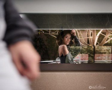 phoenix senior walking by a window looking at herself. Example of creative portraiture