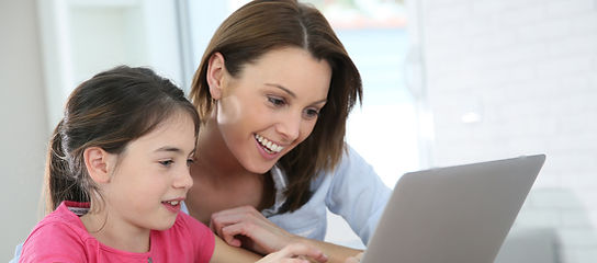Woman with girl doing homework on laptop