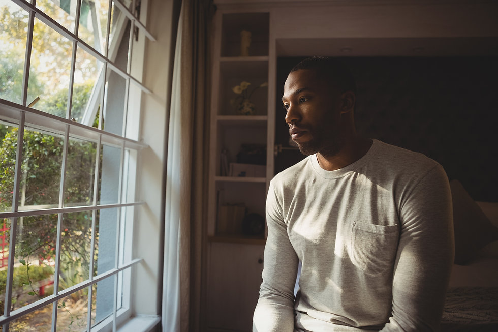 thoughtful-man-sitting-by-window-at-home