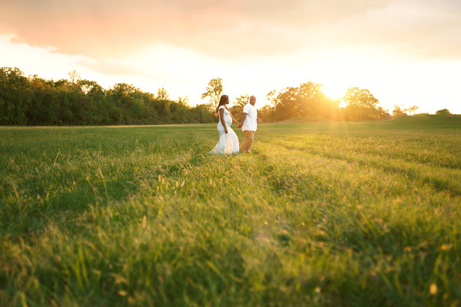 portrait of maternity couple walking in a field of grass at sunset