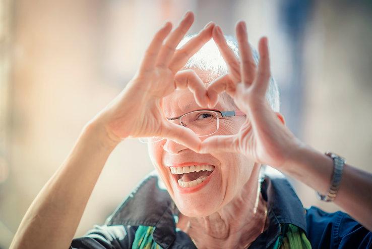 Cute senior old woman making a heart sha