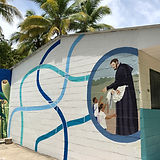 Image of a mural on the side of a school building of St. Jerome with school children. Painted ribbons of different shades and hues of blue surround the mural.