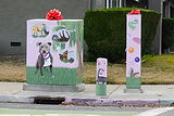 Image of a painted electrical boxes on a street corner. The painting depicts scenes of a dog's thoughts. Playing with other dogs, napping, fetching a stick, and colorful balls!