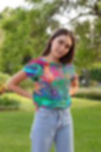 a young girl in a colorful swirl design crop top standing outside