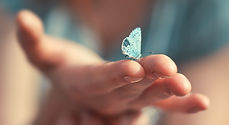 Butterfly sits on a woman hand. Blue, fr