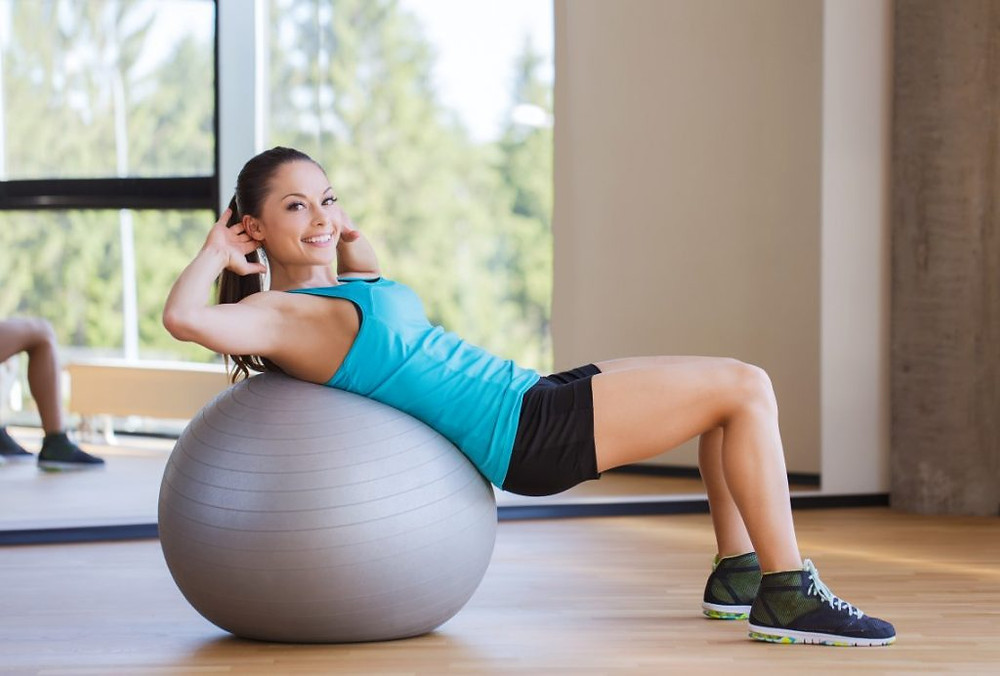 smiling woman with fit ball flexing muscles in gym