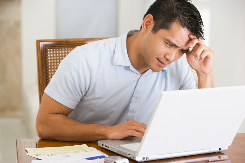 Man in dining room using laptop and frowning