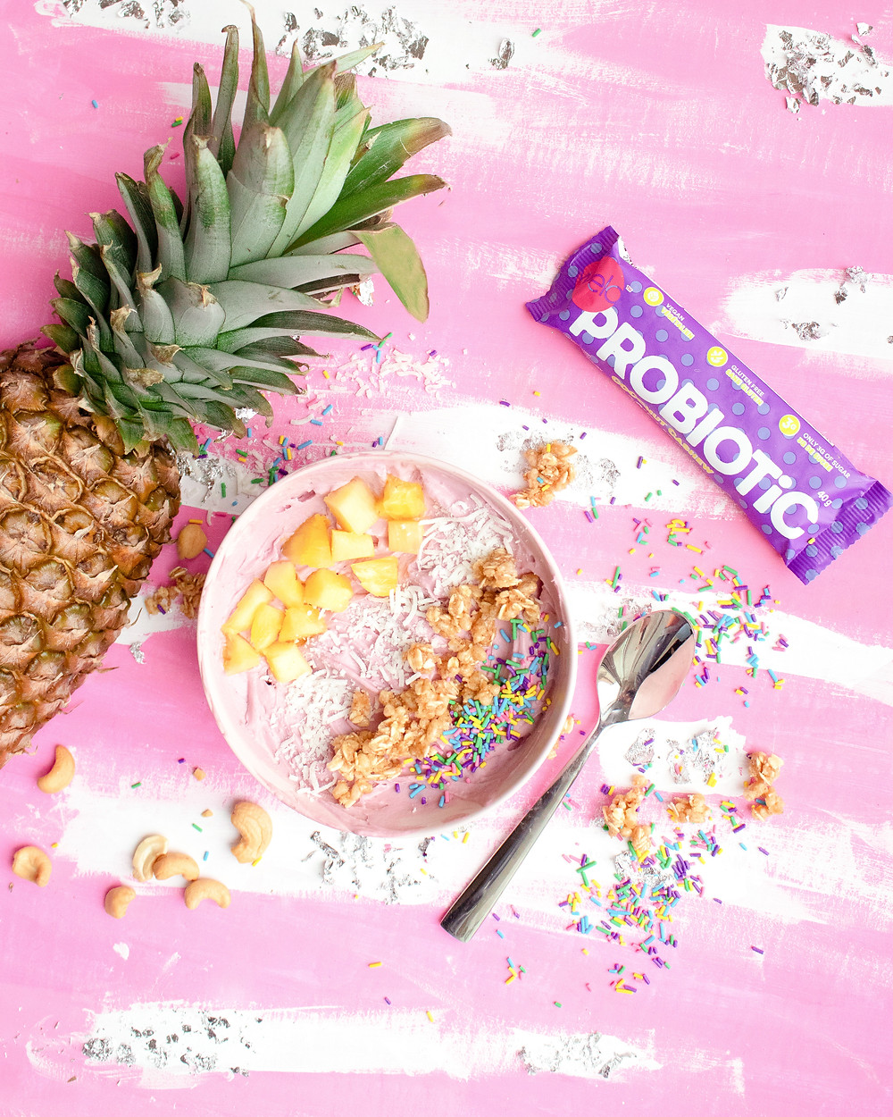 a breakfast bowl, a pineapple, a probiotic bar and a spoon